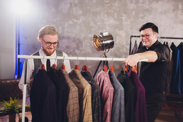 Shop assistant helping man to choose a jacket