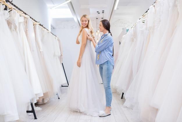 Продавец-консультант помогает женщинам застегнуть платье