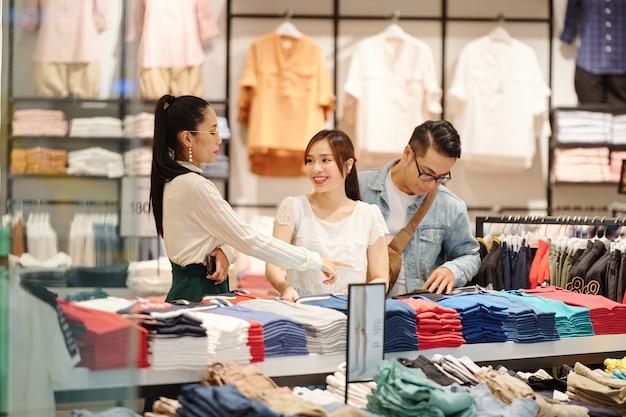 デパートで若いカップルが洋服を選ぶのを手伝う店員