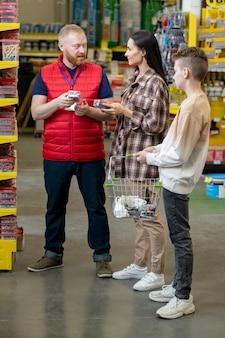 Продавец в униформе консультирует потребителей в хозяйственном супермаркете