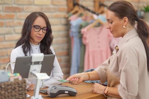 점원은 여성 고객의 비접촉식 결제를 수락하면서 컴퓨터 모니터를 바라보고 있습니다.