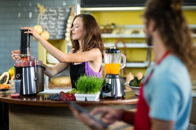 Продавец готовит сок в продуктовом магазине здоровья