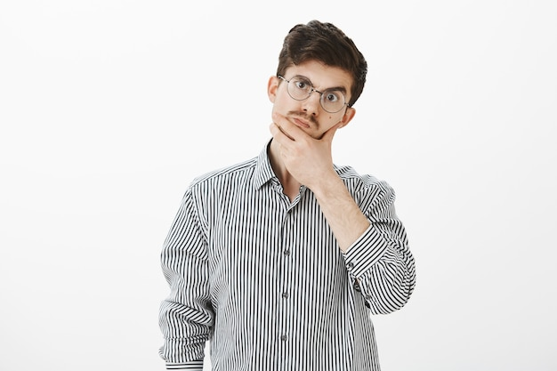 Shop assistant troubled to answer on question. confused unaware ordinary european guy in casual shirt and glasses, rubbing chin and lifting eyebrow, thinking and weighing chances on success