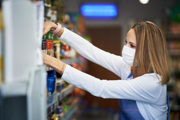 식료품 점에서 의료 마스크에서 일하는 가게 조수