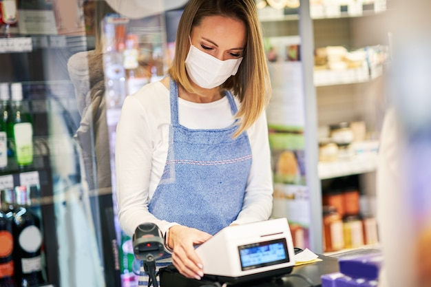 Shop assistant working in medical mask in grocery store