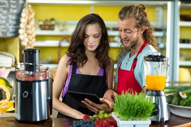 Продавцы обсуждают с цифровым планшетом в продуктовом магазине