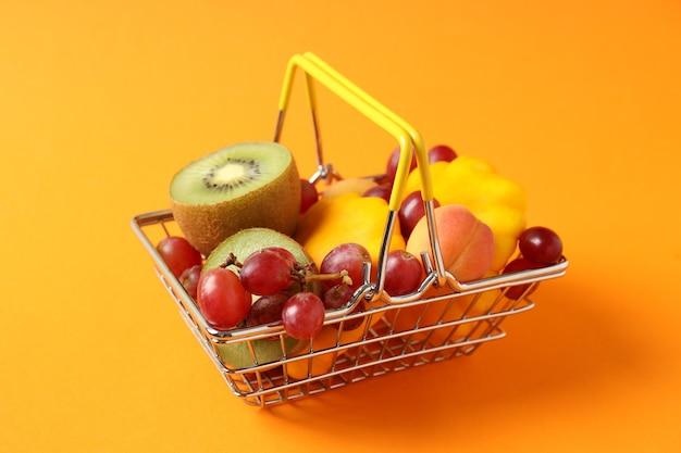 주황색 배경에 야채와 과일이 있는 쇼핑 바구니