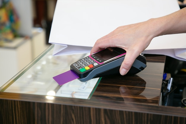 결제 과정을 진행하는 동안 고객에게 pin 코드를 입력하도록 제안하는 점원. 자른 샷, 손의 근접 촬영입니다. 쇼핑 또는 구매 개념