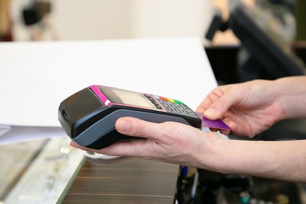 レジ係が支払いプロセスを操作し、pos端末にクレジットカードを挿入します。クロップドショット、手のクローズアップ。ショッピングや購入のコンセプト