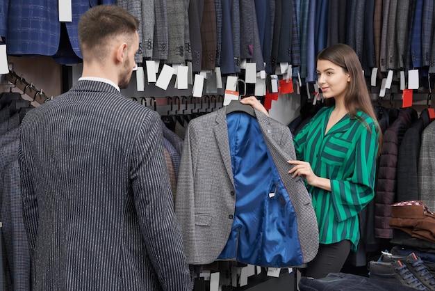 Консультант магазина выбирает и показывает куртку клиенту.