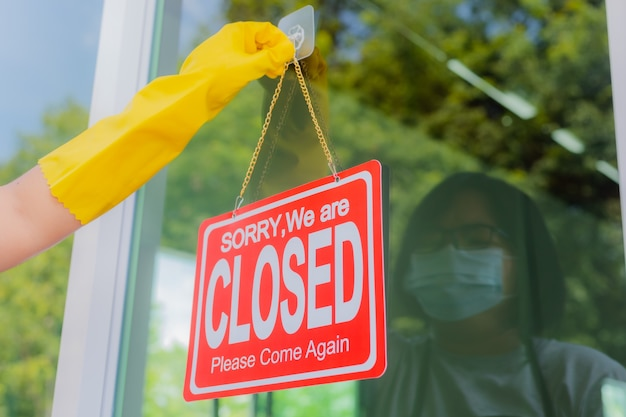 The shop owner hangs a sign to close the business in front of the door.
