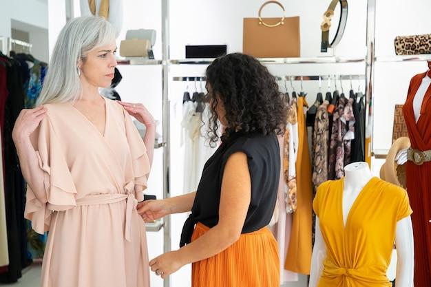 Venditore del negozio che regola il nuovo vestito sul cliente femminile. donna che prova sui vestiti nel negozio di moda. acquisto di vestiti nel concetto di boutique