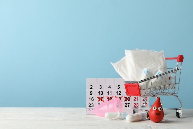 Магазинная тележка с аксессуарами менструального периода на деревянном столе, копией пространства
