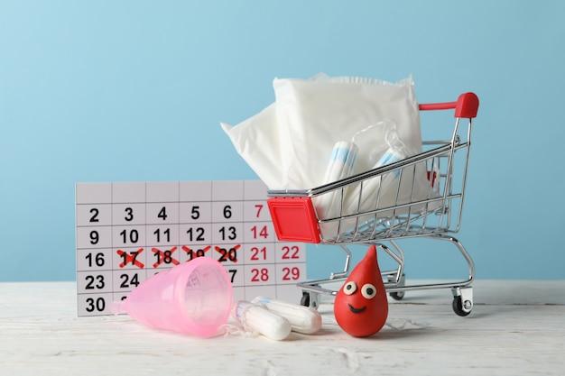 Магазинная тележка с аксессуарами менструального периода на деревянном столе