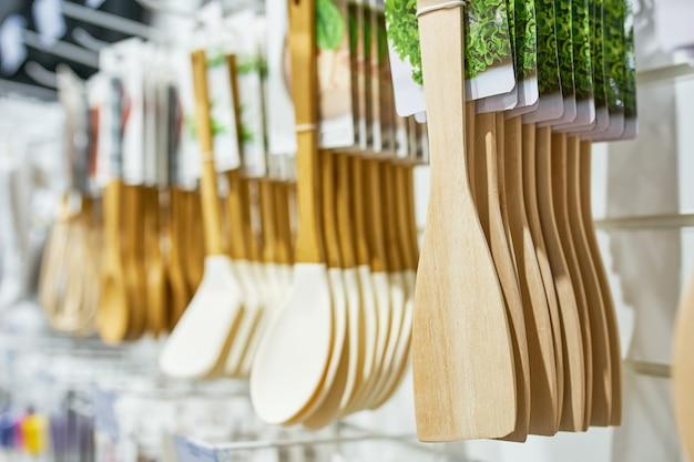 Витрина магазина с деревянной кухонной утварью, продажа товаров для дома, кухонные лопатки, висят в ряд
