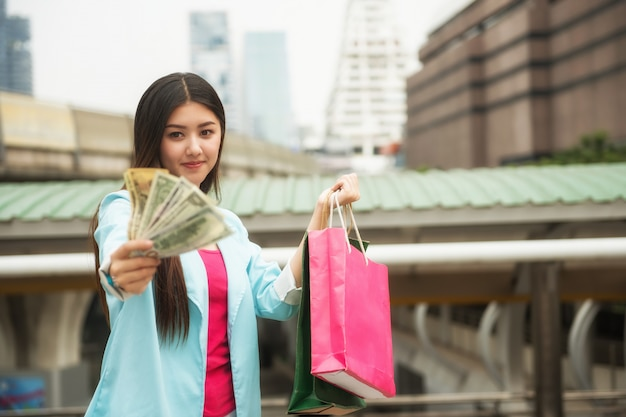 Shopaholic girl with us banknotes in city