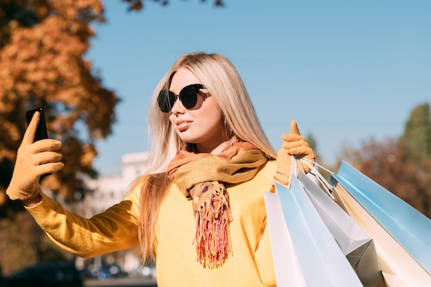 Shopaholic leisure stylish lady walking with packages, taking selfie on smartphone