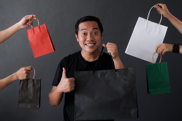 買い物袋を持って多くの手に囲まれた買い物中毒の男