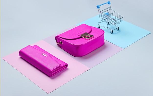 Шопоголическая минималистичная концепция. сумка, кошелек, мини-тележка для покупок на пастельном фоне. вид сбоку