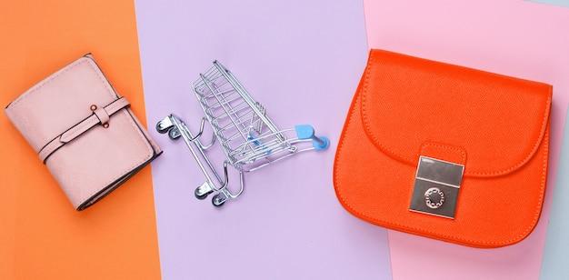 Шопоголическая минималистичная концепция. сумка, кошелек, мини-тележка для покупок на пастельном фоне. вид сверху