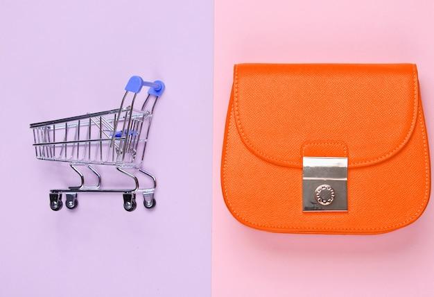 쇼핑 중독 최소한의 개념. 노란색 가방, 파스텔 배경에 미니 쇼핑 트롤리. 평면도