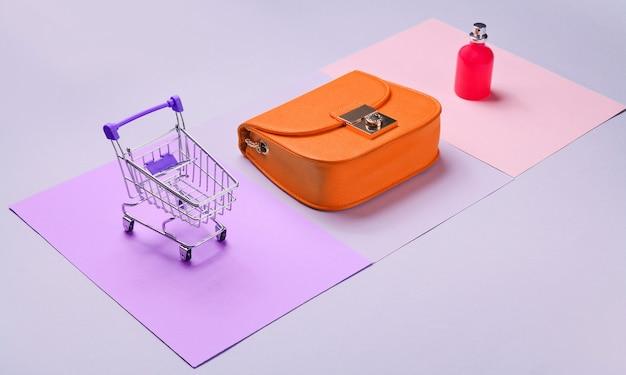買い物好きのミニマルなコンセプト。パステルカラーの背景に黄色のバッグ、香水瓶、ミニショッピングトロリー。側面図