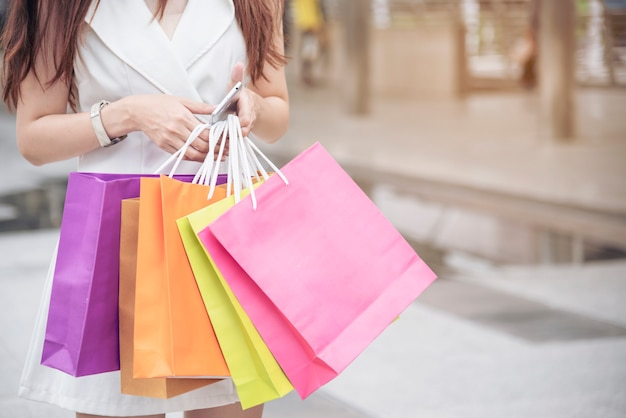 Shopaholic woman holding shopping bags ,money ,credit card at shopping malls