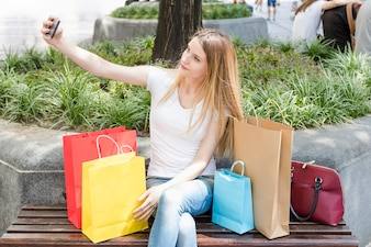 Shopaholic woman sitting on bench taking selfie on smartphone