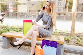 Shopaholic woman sitting on bench talking on cellphone