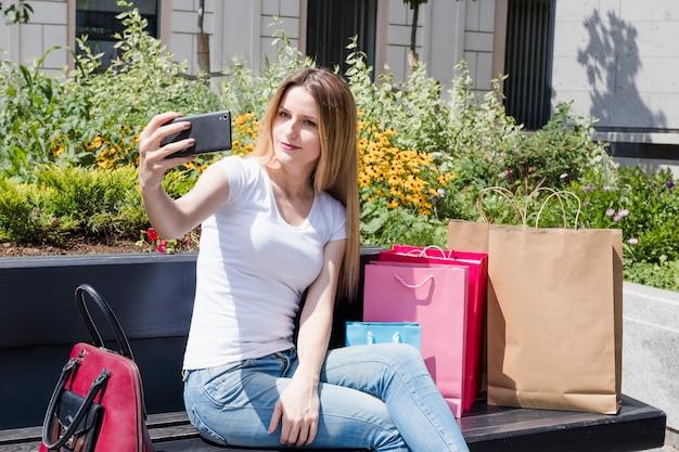Donna di shopaholic che prende selfie sullo smartphone