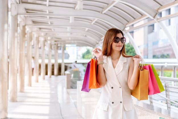 쇼핑 몰에서 쇼핑백을 들고 쇼핑 중독 여성입니다. 유행 여자는 쇼핑 라이프 스타일을 사랑