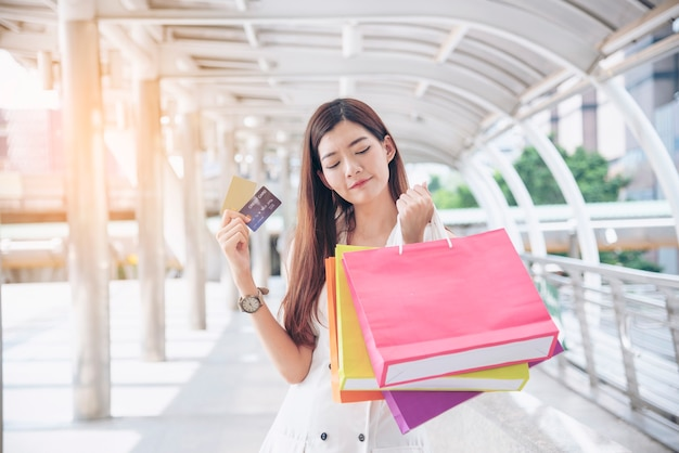 쇼핑몰에서 쇼핑백을 들고 있는 쇼핑중독 여성.