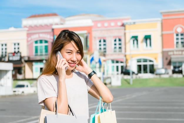 美しい若いshopaholicアジアの女性が話すためにスマートフォンを使用して