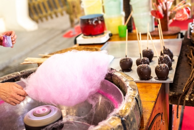 Shopkeeper preparing a candy cotton cloud at a fair for some children.