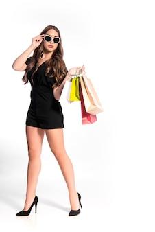 Девушка покупателя изолирована на белом, кавказская молодая женщина в покупках