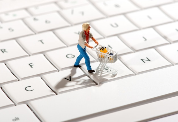 Shopper pushing a trolley over a computer keyboard