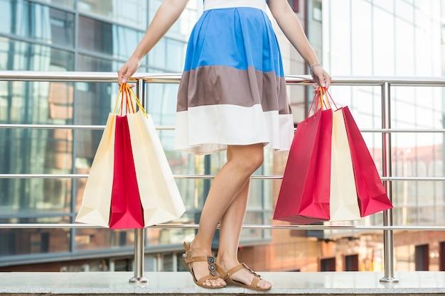 Покупатель. шопоголик торговый женщина, держащая много возбужденных хозяйственных сумок. концепция зависимости