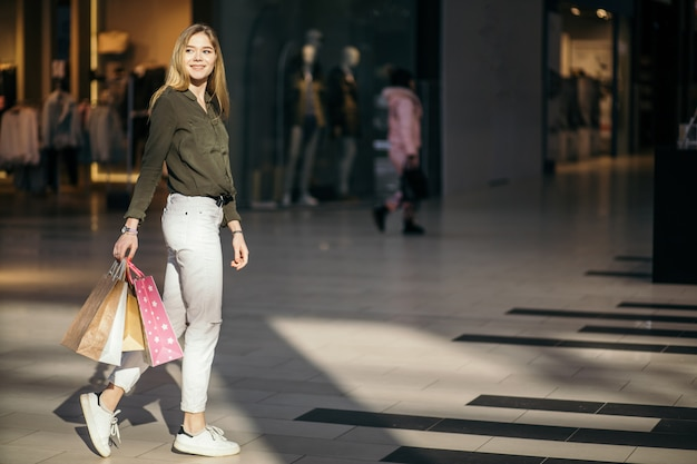 Shopper walking in trade center or mall with shopping bags