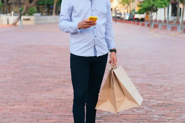 거리에 휴대폰과 선물 가방을 든 쇼핑객