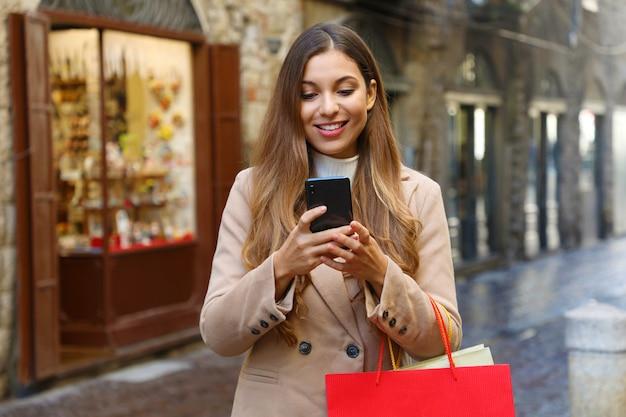 Женщина покупателя покупает онлайн с умным телефоном на улице старого города зимой.