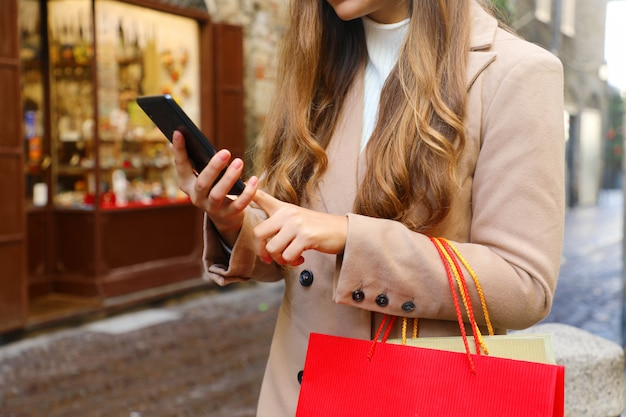 Shopper woman using smart phone for shopping online in the street.