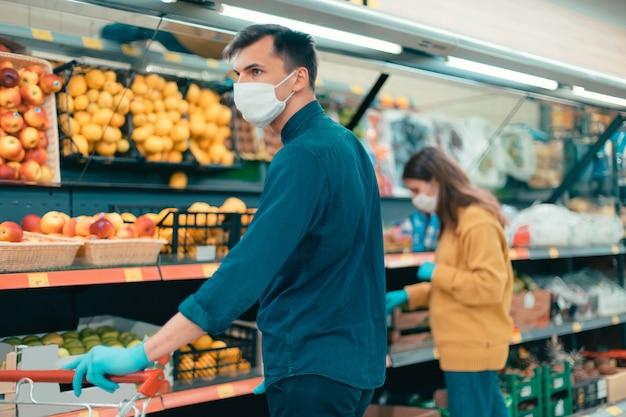 スーパーマーケットで果物を選ぶ保護マスクの買い物客。市内のコロナウイルス