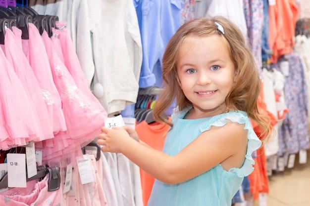 쇼핑. 소녀는 스스로 물건을 선택하고 소녀는 물건을 구입합니다.