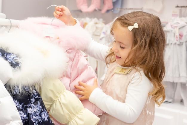 쇼핑. 아름다운 재킷으로 기뻐하는 소녀는 따뜻한 옷을 선택합니다.