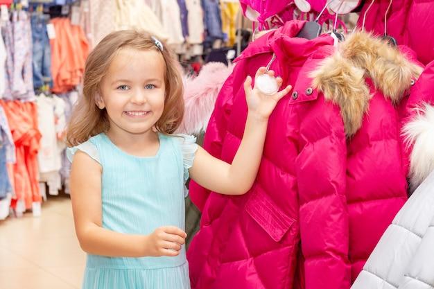 ショッピング。美しいジャケットに喜んでいる女の子は、暖かい服を選びます。