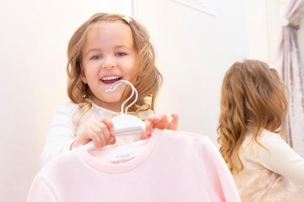 Покупка. девушка примеряет красивое платье нежно-розового цвета в примерочной бутика.