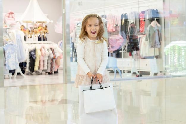 쇼핑. 손에 쇼핑백을 가진 소녀입니다. 흰색 가방 copyspace입니다.