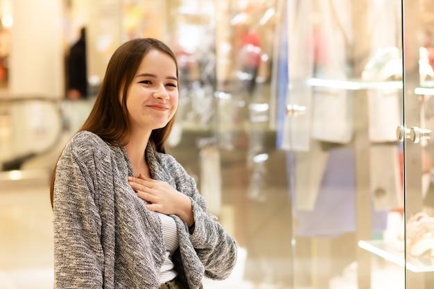 쇼핑 몰에있는 어린 소녀는 판매와 할인을 즐깁니다.