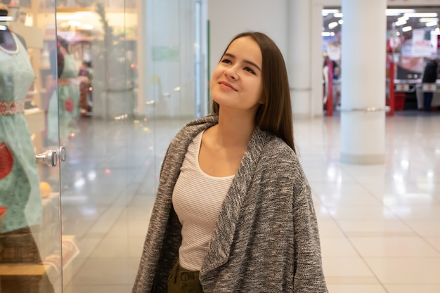 Шоппинг. молодая девушка смотрит на витрины магазинов, выбирает подарки в торговом центре.