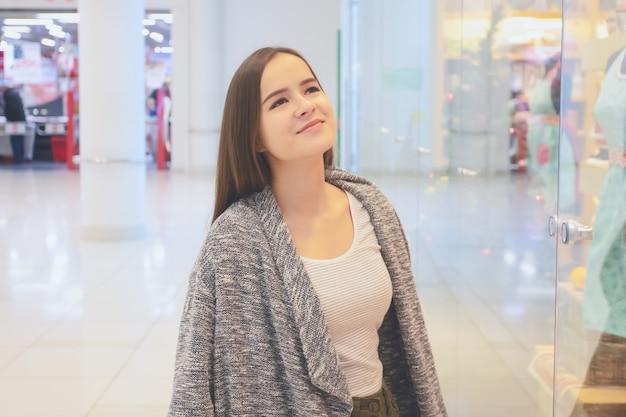 쇼핑 어린 소녀가 상점 창을 살펴보고 쇼핑몰에서 선물을 선택합니다.